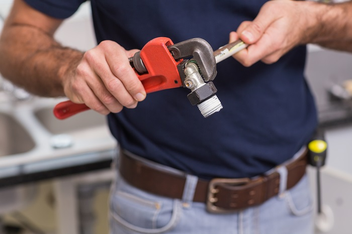 plumber holding a pipe wrench plumbing tool